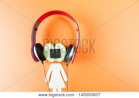 Alphanumeric apple with humanoid body listen on blue wooden background