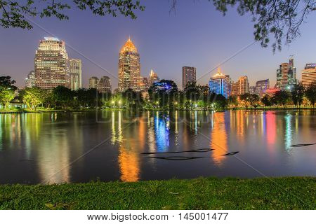 Business district cityscape from a park with Twilight Time from Lumpini Park Bangkok Thailand