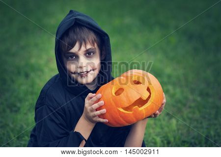 Child in scary costume with pumpkin. Child in halloween outfit playing in the garden