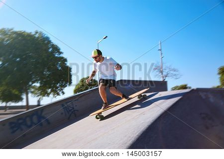 Young Man With Beard And Tattoos Skating On Longboard