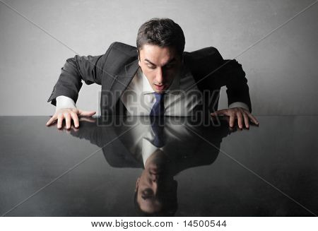 Astonished businessman looking at his reflex on a table