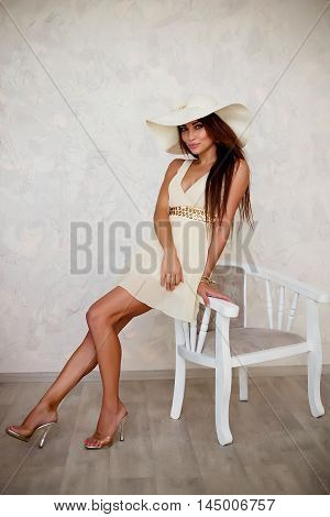 Portrait of attractive young brunette woman in white dress and high heels sitting on arm-chair in vintage room