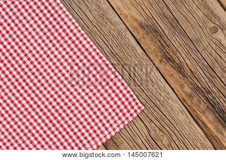 Rustic wooden boards with a red checkered tablecloth. Top view.