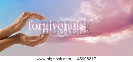 Forgive and release to your Higher Power - female hands gently cupped around the word FORGIVENESS on a soft blue sky background with a beautiful fluffy pink cloud stream and sun light