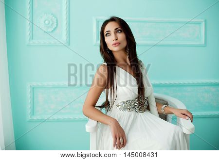 Portrait of attractive young brunette woman in white dress sitting on arm-chair in vintage room