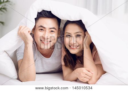 Beautiful young loving couple lying in bed together