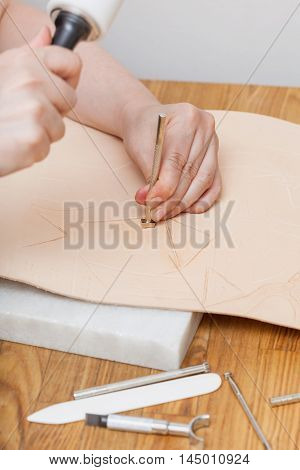 leathercraft - craftsman puts stamping on leather poster