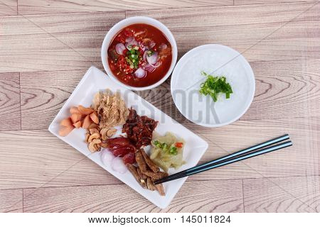 Rice gruel and  side dish  on wood. (Dried shredded pork, Chinese sausage, crispy fish, sausage, fried baby clams, sliced red onion, pickle Chinese cabbage, Spicy sardine salad and shallots )