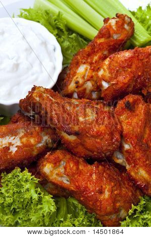 Platter of buffalo wings with a blue cheese dipping sauce and celery sticks.  Hot and spicy!