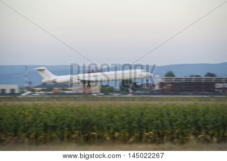 Passenger airplane landing on runway at dusk hour
