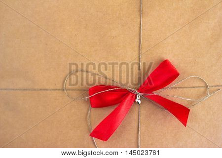 Holiday gift wrapping with a red bow on paper