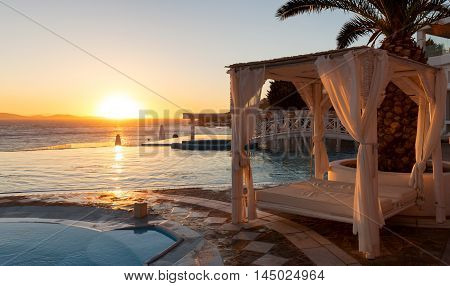 Luxury sunbed and infinity pool at sunset