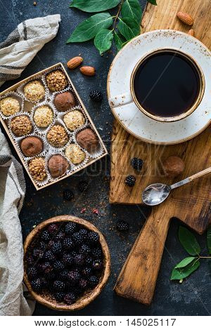 Chocolate truffles, cup of black coffee and fresh blackberries. Still life coffee time. Top view, vertical