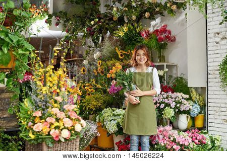 Smiling pretty florist with bouquet of roses