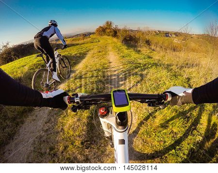 POV. Riding on mountain bike at sunset on a Tuscany countryside.