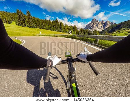 Cyclist on mountainous road in a sunny day. Cycling in Dolomites Passo Campolongo. POV Original point of view