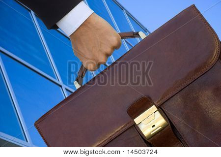 A business man with his working bag over a blue building reflection