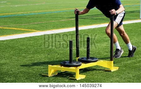 An athlete pushing a weighted sled on a green turf field