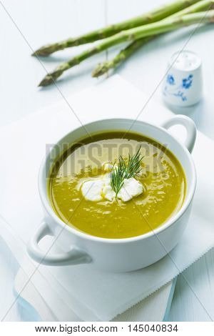 Closeup of asparagus soup in a bowl with fresh cream and dill