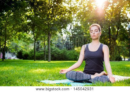 Meditating woman in meditation in city park in yoga pose. Girl relaxing with serene relaxed expression outside in summer. Beautiful young Caucasian female model. sun flare