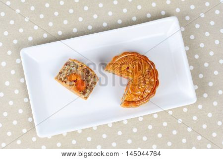 A dish of Mooncake filling five seed and salt eggs on brown.