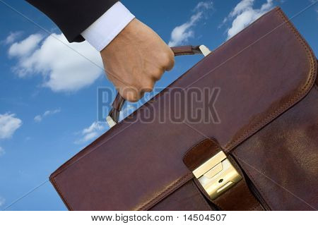 Business man with his working bag over blue sky, symbol of job recruitment and opportunity.