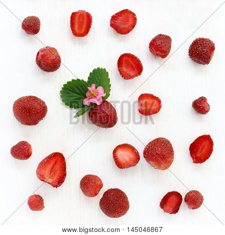 flat layout with red strawberries on a light wooden background / strawberry background with flower