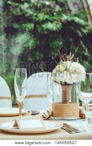 Table set for an event party or wedding reception banquet. Winter bridal bouquet of white carnations peony roses flowers with twine in vase on table craft background. Elegant wine glass cutlery napkin. Rustic style.