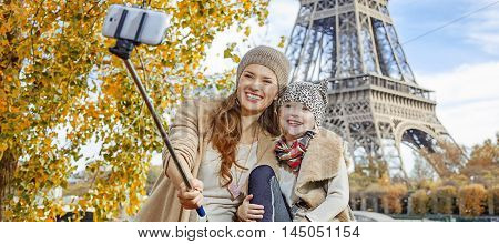 Mother And Child Tourists Taking Selfie On Embankment In Paris