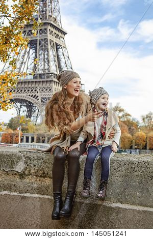 Mother And Daughter On Embankmen In Paris Pointing On Something