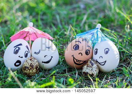 Funny eggs imitating two couples and surprised white parent of versicolored baby