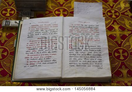 open old Bible written in Old Church Slavonic language church on red cloth with crosses