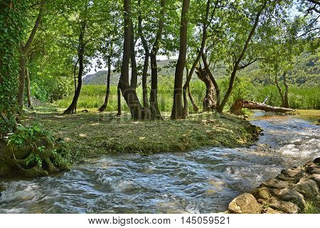 The landscape near Roski Slap waterfall showing a small tributary of the River Krka in Krka National Park Sibenik-Knin County Croatia.