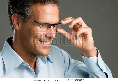 Handsome mature man holding a pair of modern glasses