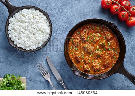 Traditional Madras butter Beef spicy slow cook lamb food with rice and tomatoes in cast iron pan on blue table background. Delicious India culture restaurant dish.
