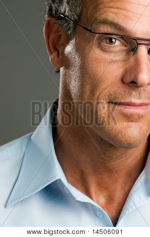 Portrait of half mature man looking at camera with a pair of glasses.