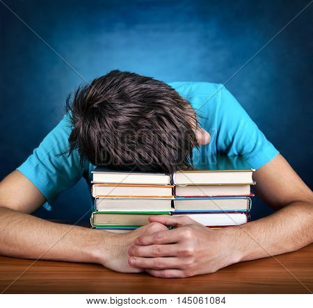 Tired Teenager sleep on the Books on the Blue Background
