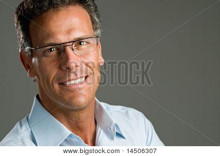 Volwassen man op zoek naar camera met een lichte glimlach en een paar glazen. Ruimte voor tekst