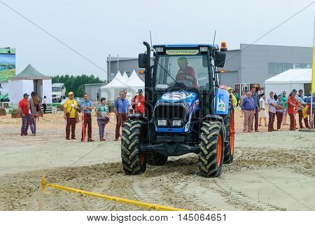 Tyumen, Russia - June 24, 2016: The 5th open championship of Russia on a plowed land. Tractor operator participates in competition on driving speed on special track for slalom