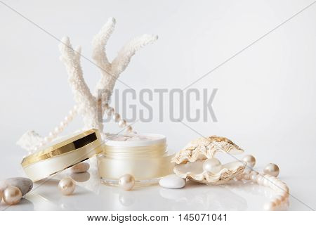 Nameless cosmetic jar and pearl in shell decorated with pearl necklace on white background