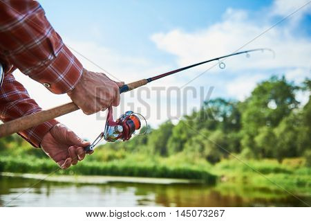 Fisherman holding spinning rod with reel while fishing