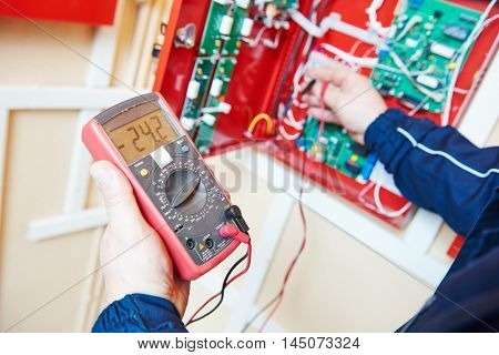 electrician work with multimeter tester