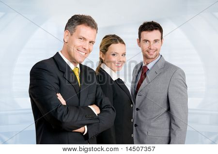 Three happy business colleagues standing together and looking at camera in their modern office