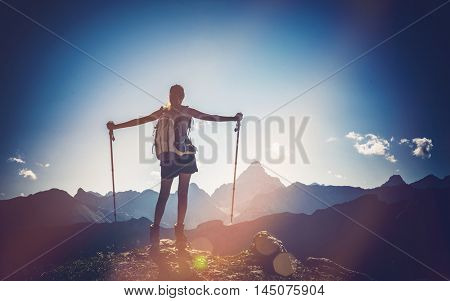 Female mountain climber stands triumphantly at summit with arms stretched to either side looking out towards ranges