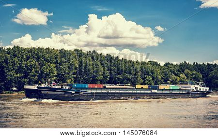 Cargo ship with containers on the Danube river Slovak republic. Goods transport. Blue retro photo filter. Freight transportation. Against the flow. Clouds in the sky.