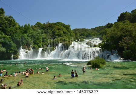 Skradin Croatia - July 2nd 2016. Tourists swim in the waters of Skradinski Buk waterfall on the River Krka in Krka National Park Sibenik-Knin County Croatia. The waterfall consists of travertine barriers and a total of 17 different water falls it is consi