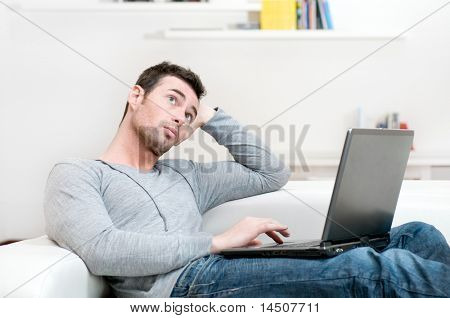 Pensive young man looking up while working on laptop at home
