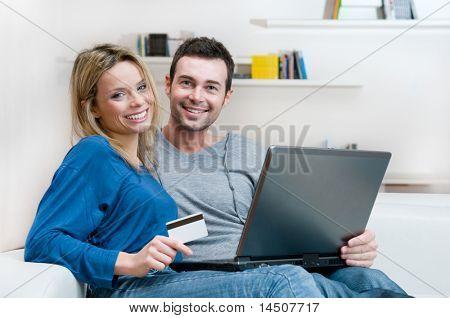 lächelnd junges paar Making online-shopping mit Kreditkarte und Laptop zu Hause
