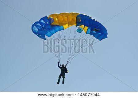 Kharkiv Ukraine - August 20 2016: Skydiver flying on colorful parachute at the airfield Korotych Kharkov region Ukraine on August 20 2016