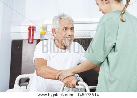 Nurse Helping Smiling Senior Man In Using Walker